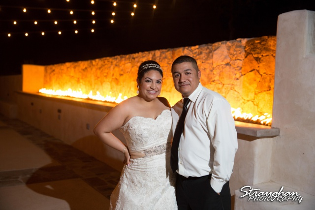 Alex wedding Lost Mission bride and groom standing in front of the fire