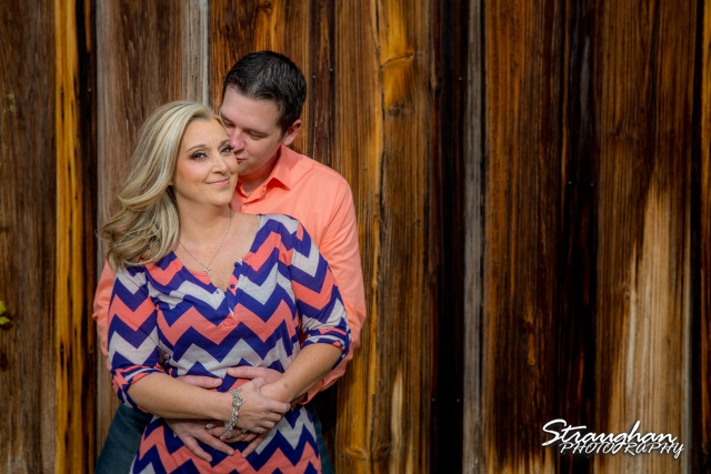 Heather engagement Gruene hugging on wooden wall