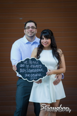 Derrick- Jessica Engagement at the Pearl holding sign