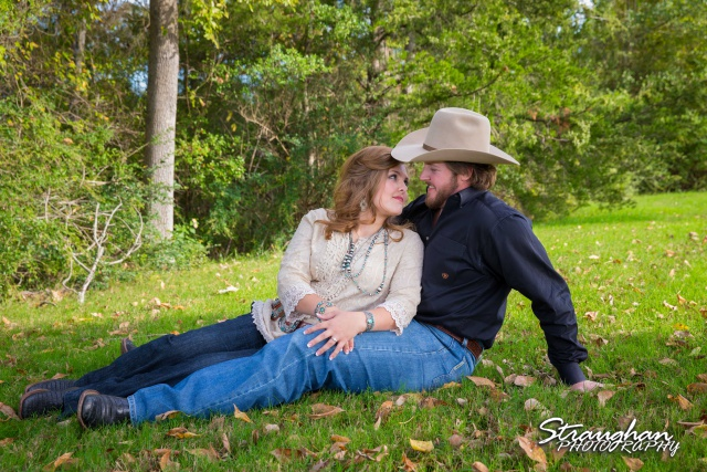 Lauren and Micah engagement Texas A&M sitting in grass