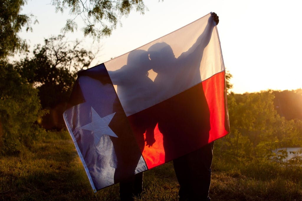 engagement photo, kissing with texas flag as a cover