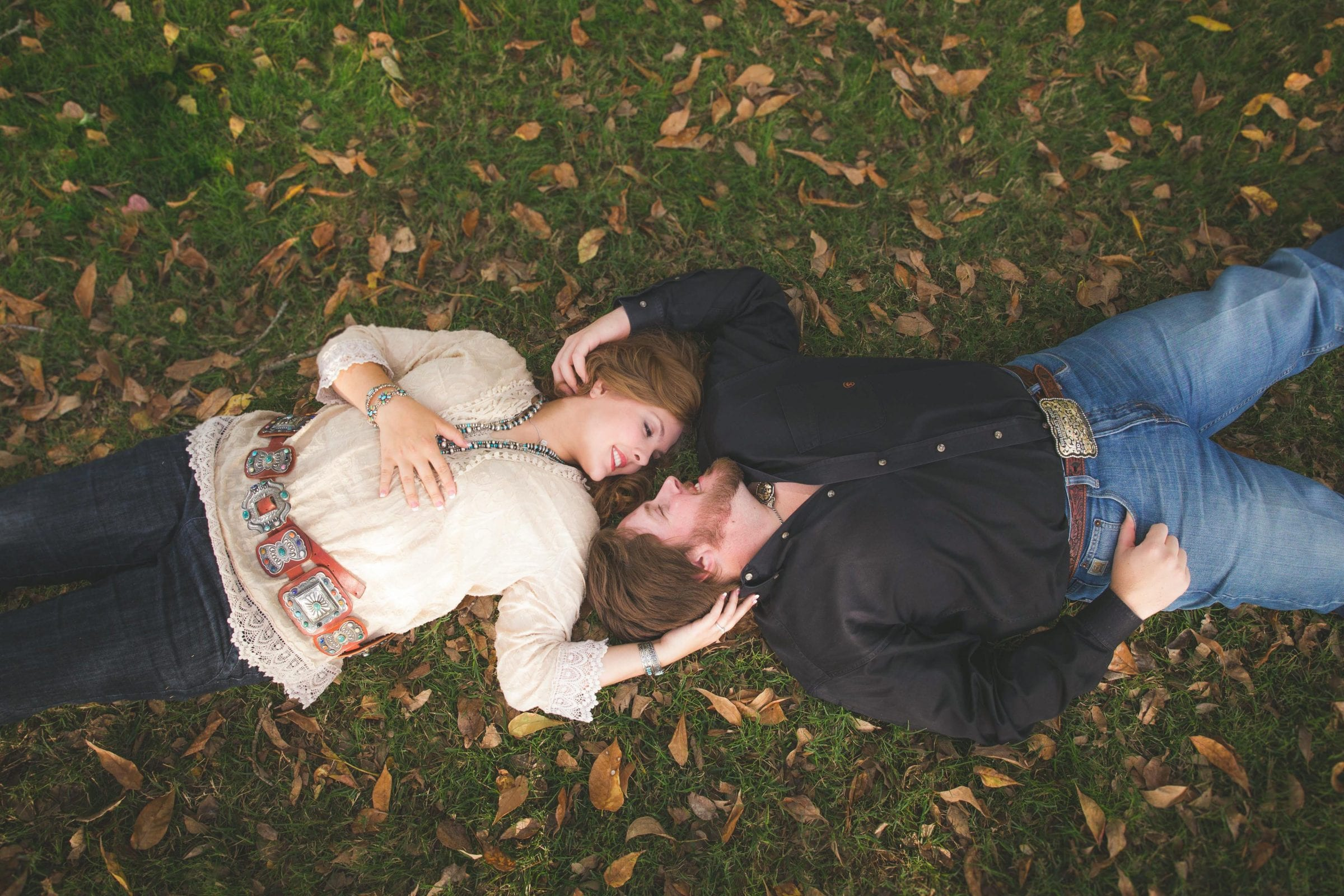 engagement photo laying down on the grass