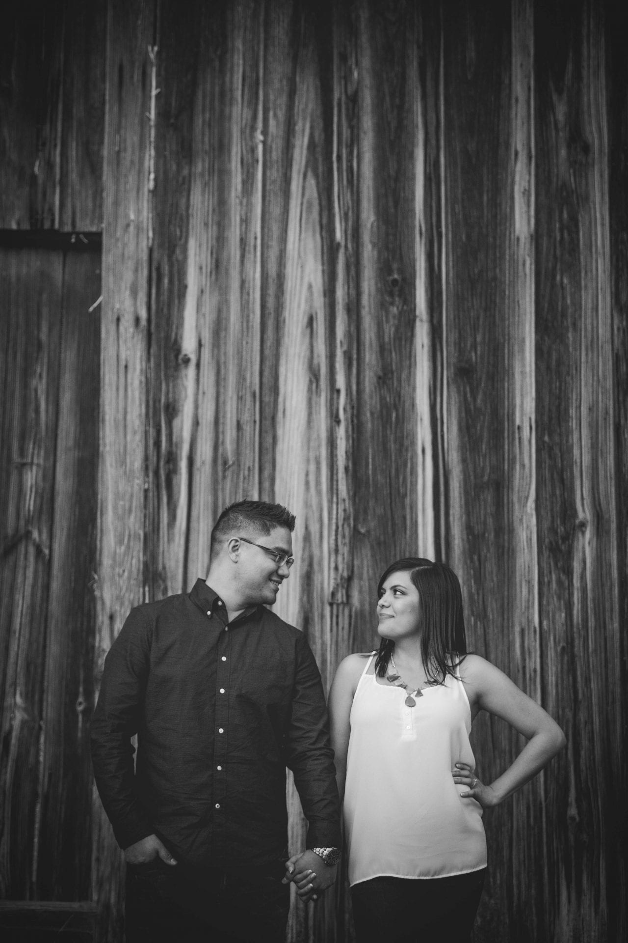 black and white engagement photo, couple standing in front of wood panels