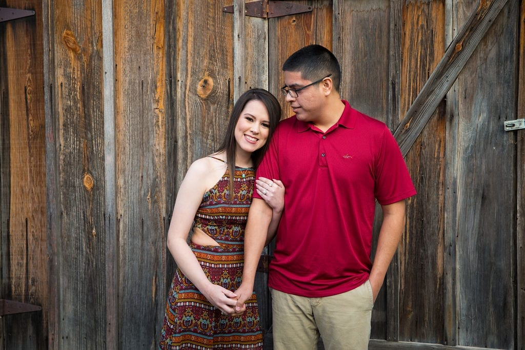 Aamber and Alex engagement session in Gruene Tx on wooden wall red