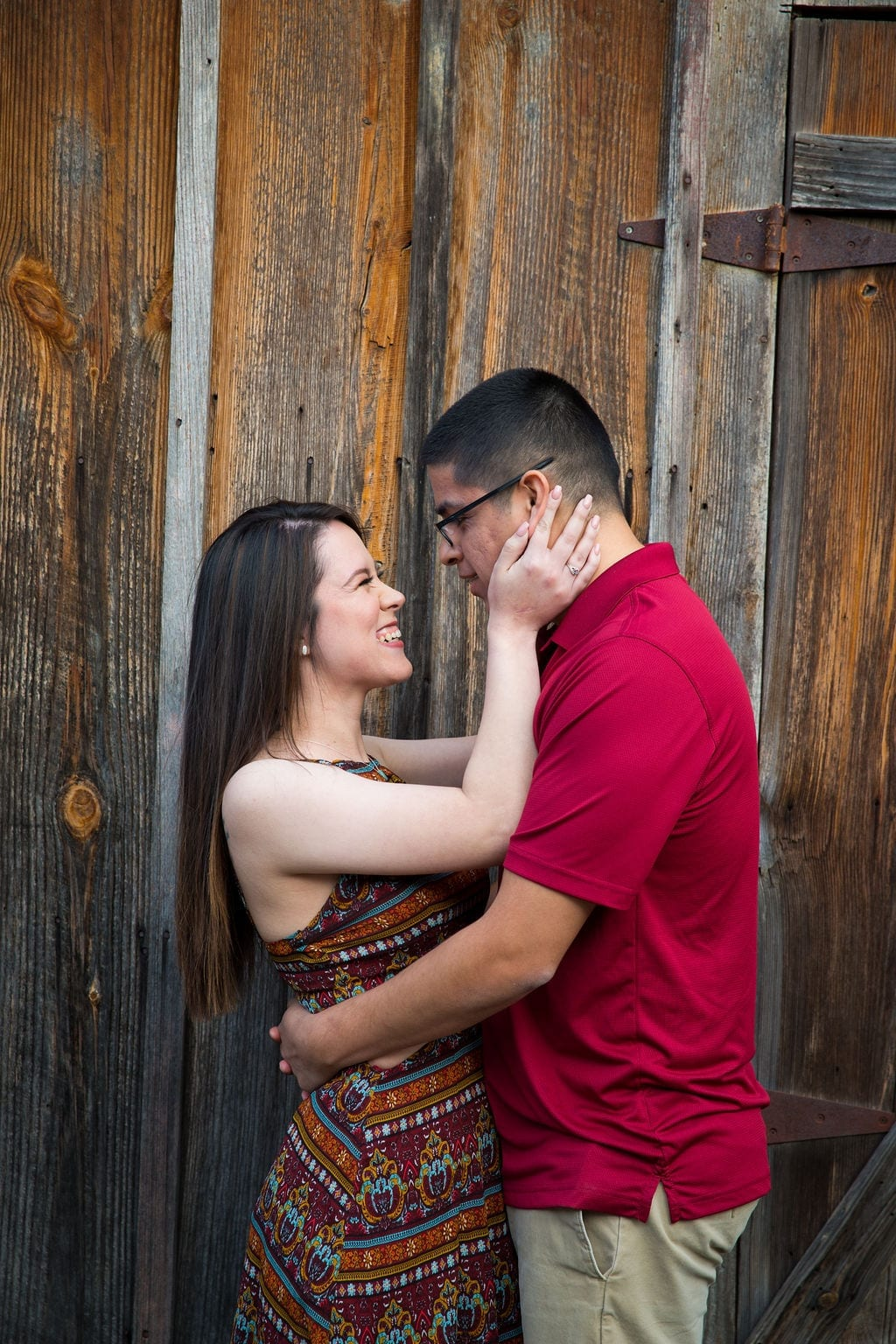 Aamber and Alex engagement session in Gruene Tx on wooden wall looking at each other
