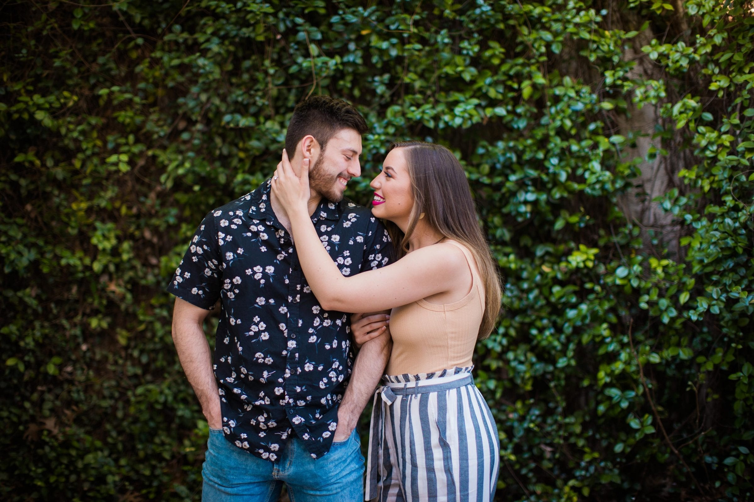 Liz and Ruben engagement standing on greenery wall downtown New Braunfels