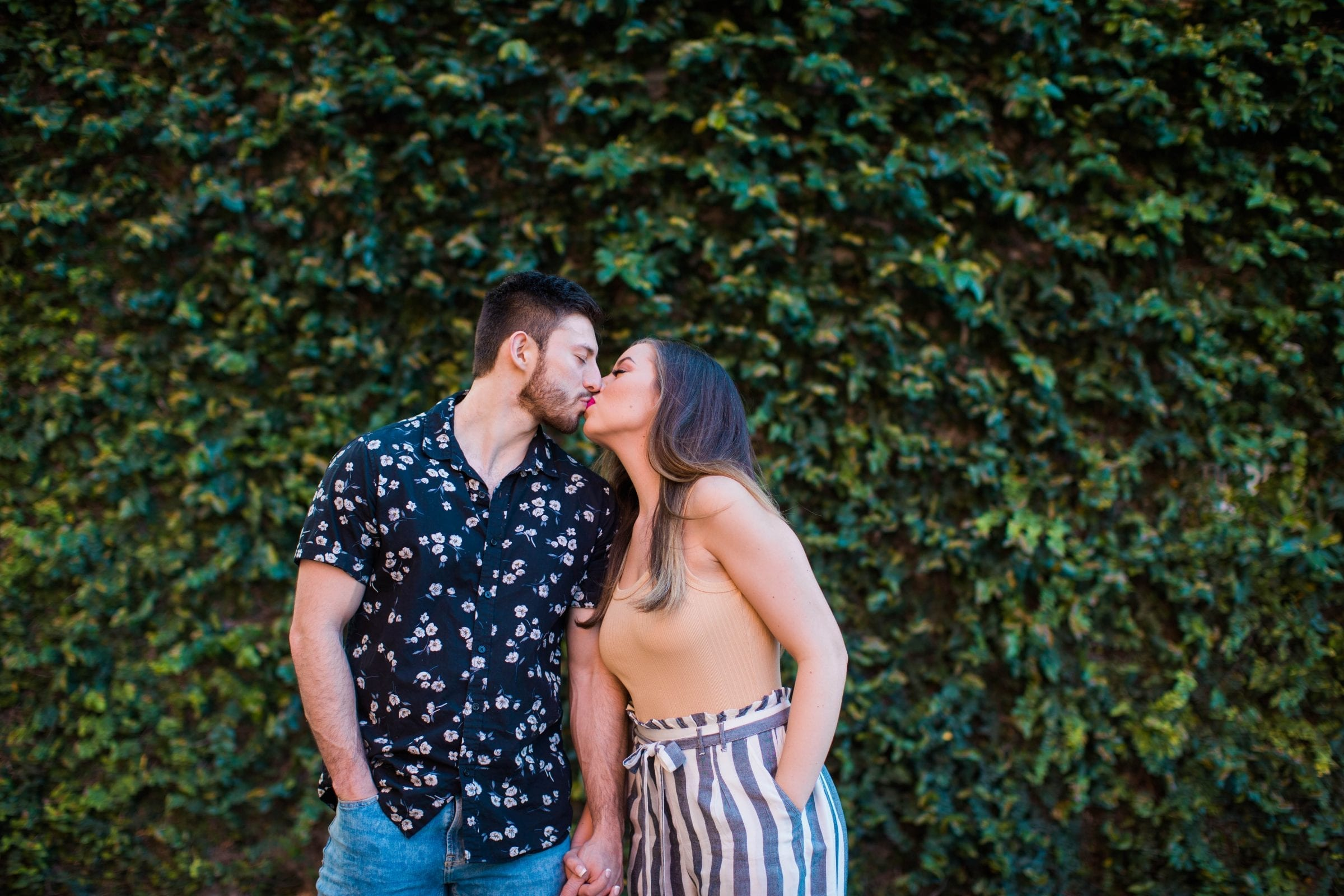 Liz and Ruben engagement kissing on greenery wall downtown New Braunfels