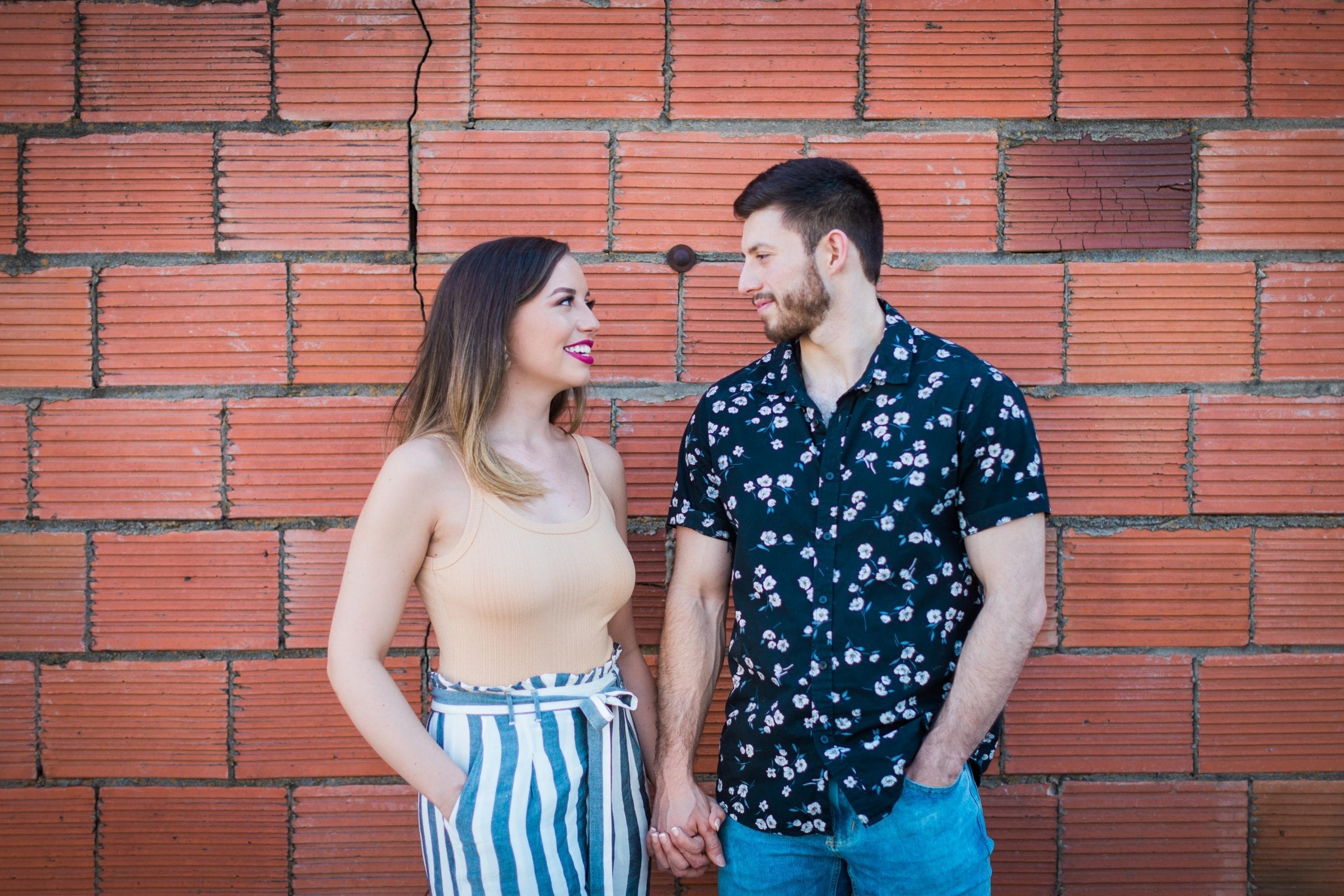 Liz and Ruben engagement looking at each other on red brick wall downtown New Braunfels