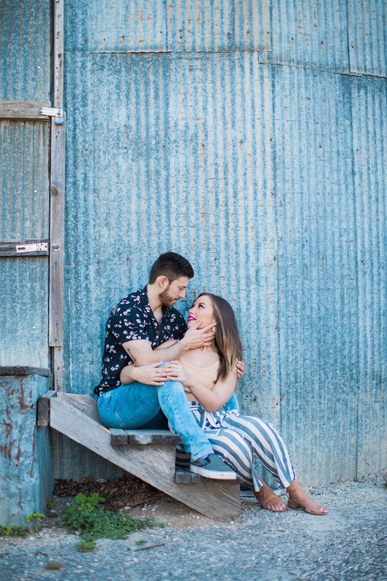 Liz and Ruben engagement looking at each other on tin wall downtown New Braunfels