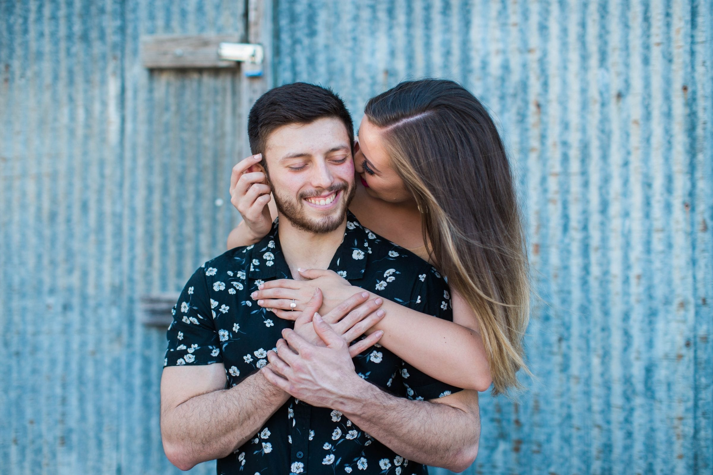 Liz and Ruben engagement kissing on tin wall downtown New Braunfels