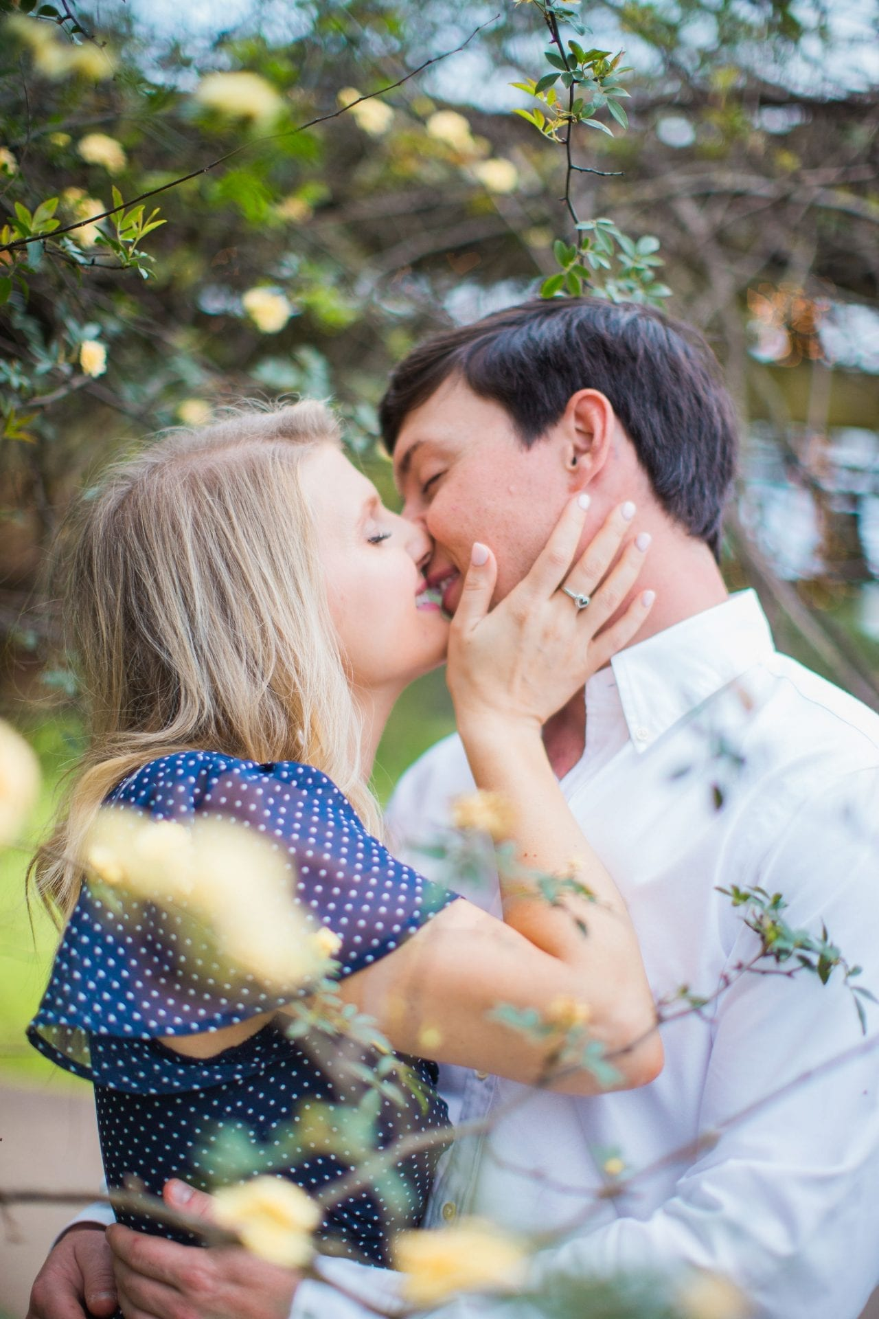 Michele Engagement session in the yellow flowers kissing at Oak Valley Vineyards