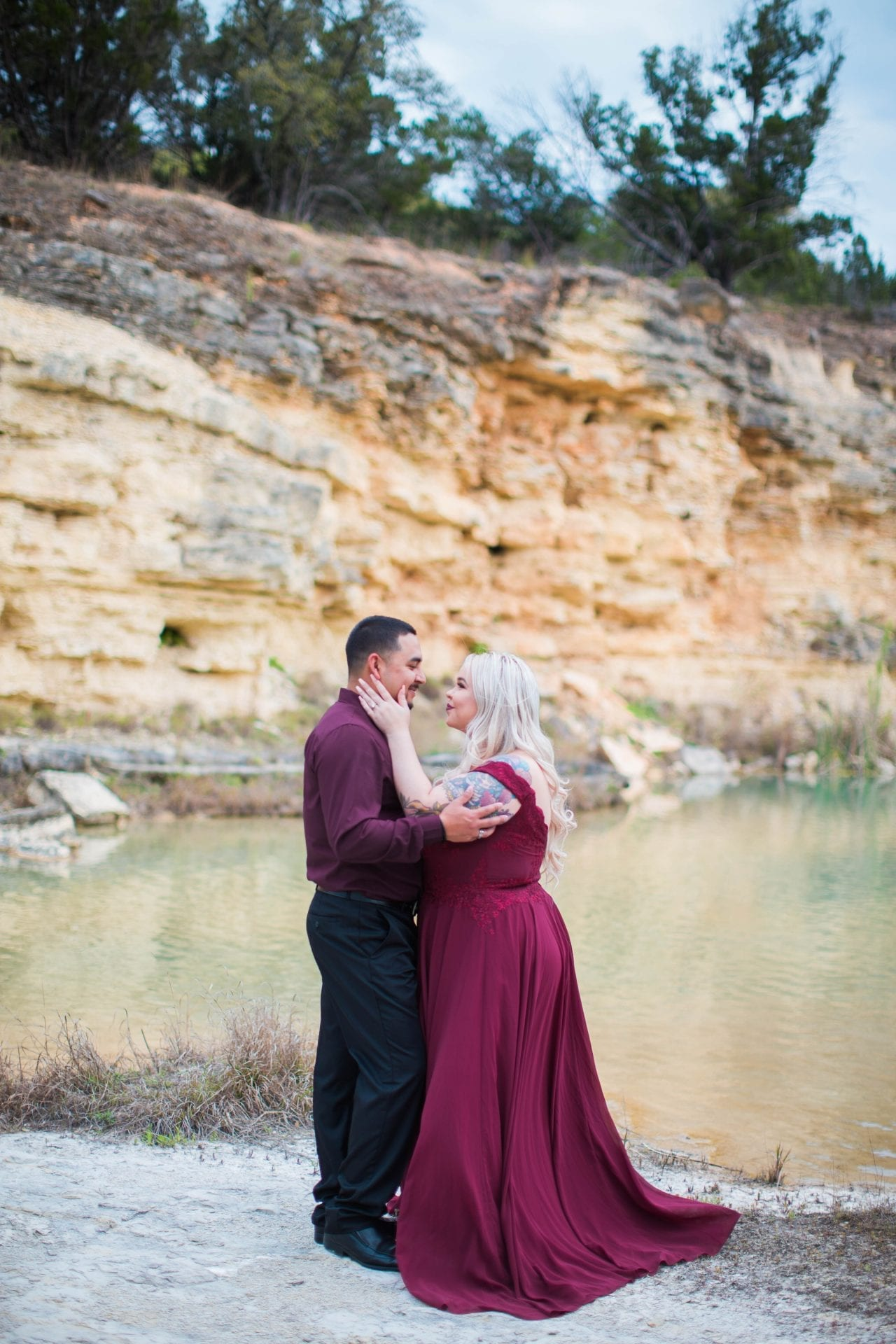Katie and Gabe engagement session Canyon Lake dam gorge on the island yellow wall looking at each other