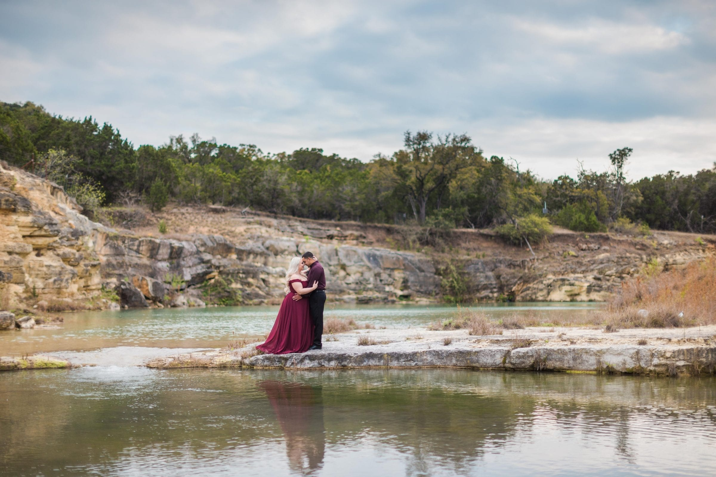 Katie and Gabe engagement session Canyon Lake dam gorge on the island looking at ea other at water fall