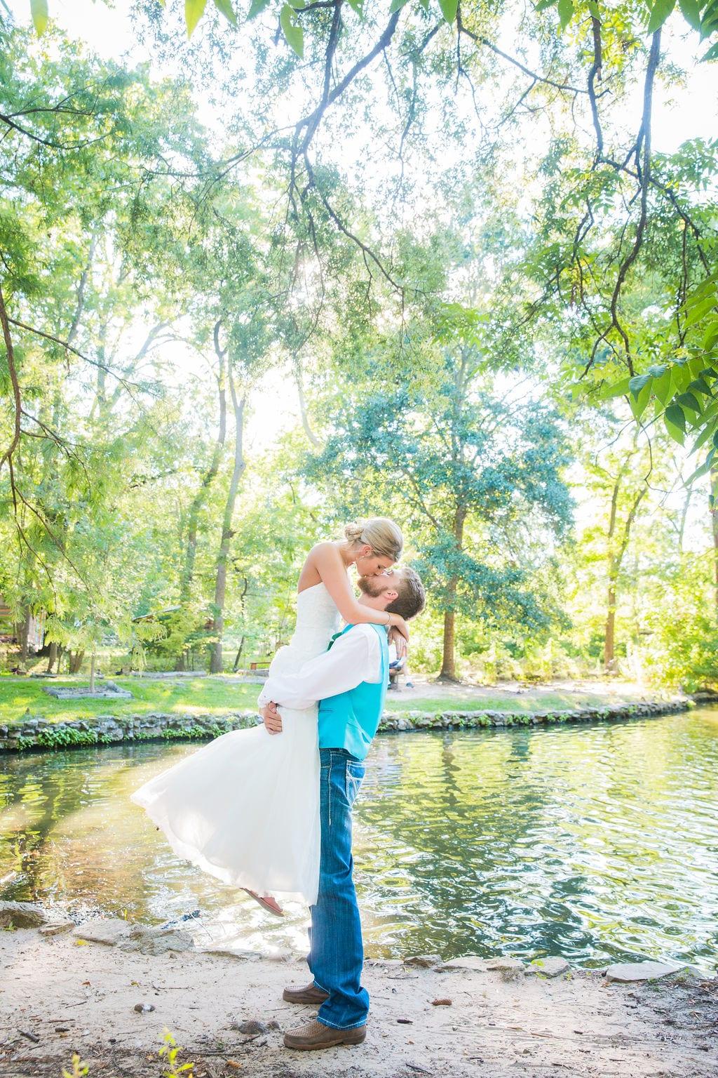 Courtney and Bearen's Wedding couple by pond him holding her up