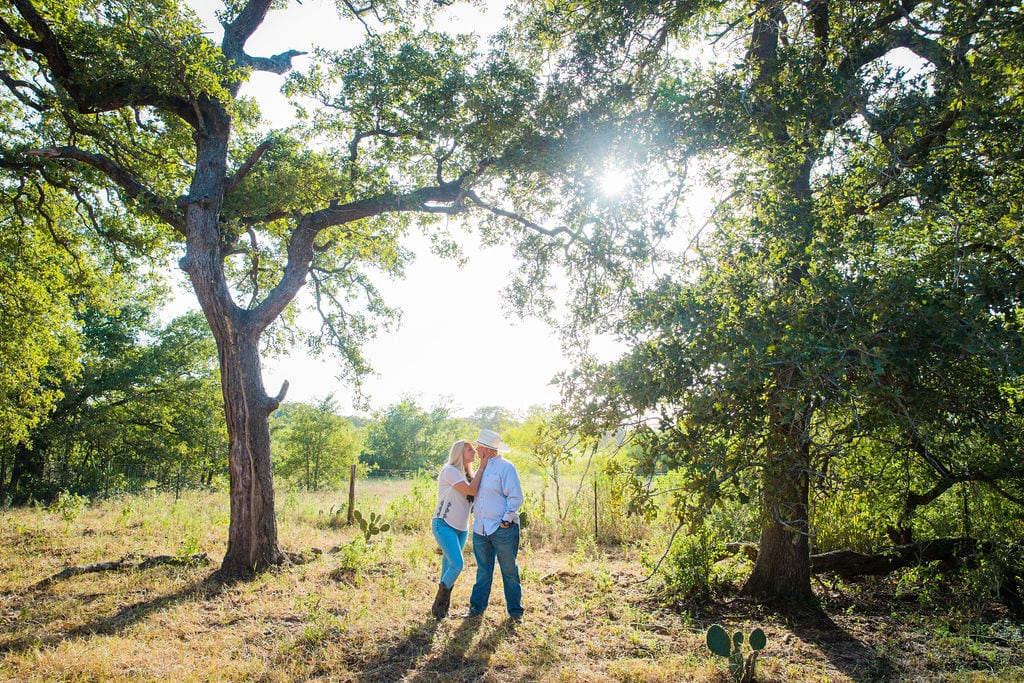 Whitney and Craig's ranch Engagement session under the tree kissing