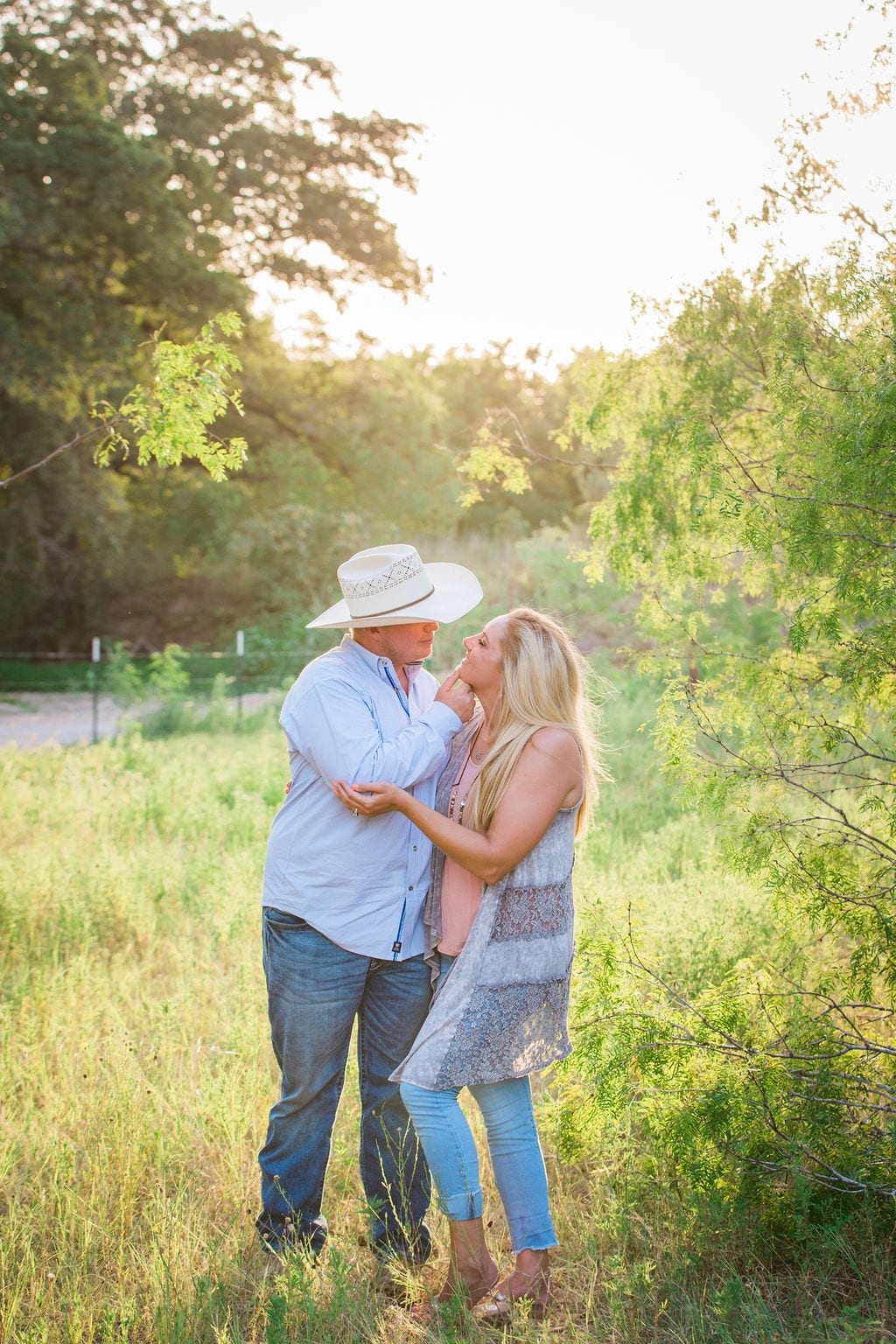 Whitney and Craig's ranch Engagement session back lit holding chin