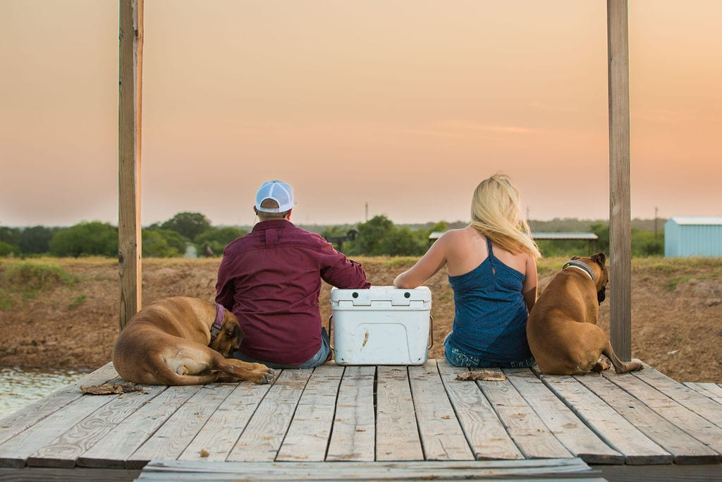 Whitney and Craig's ranch Engagement session on the dock with the dogs