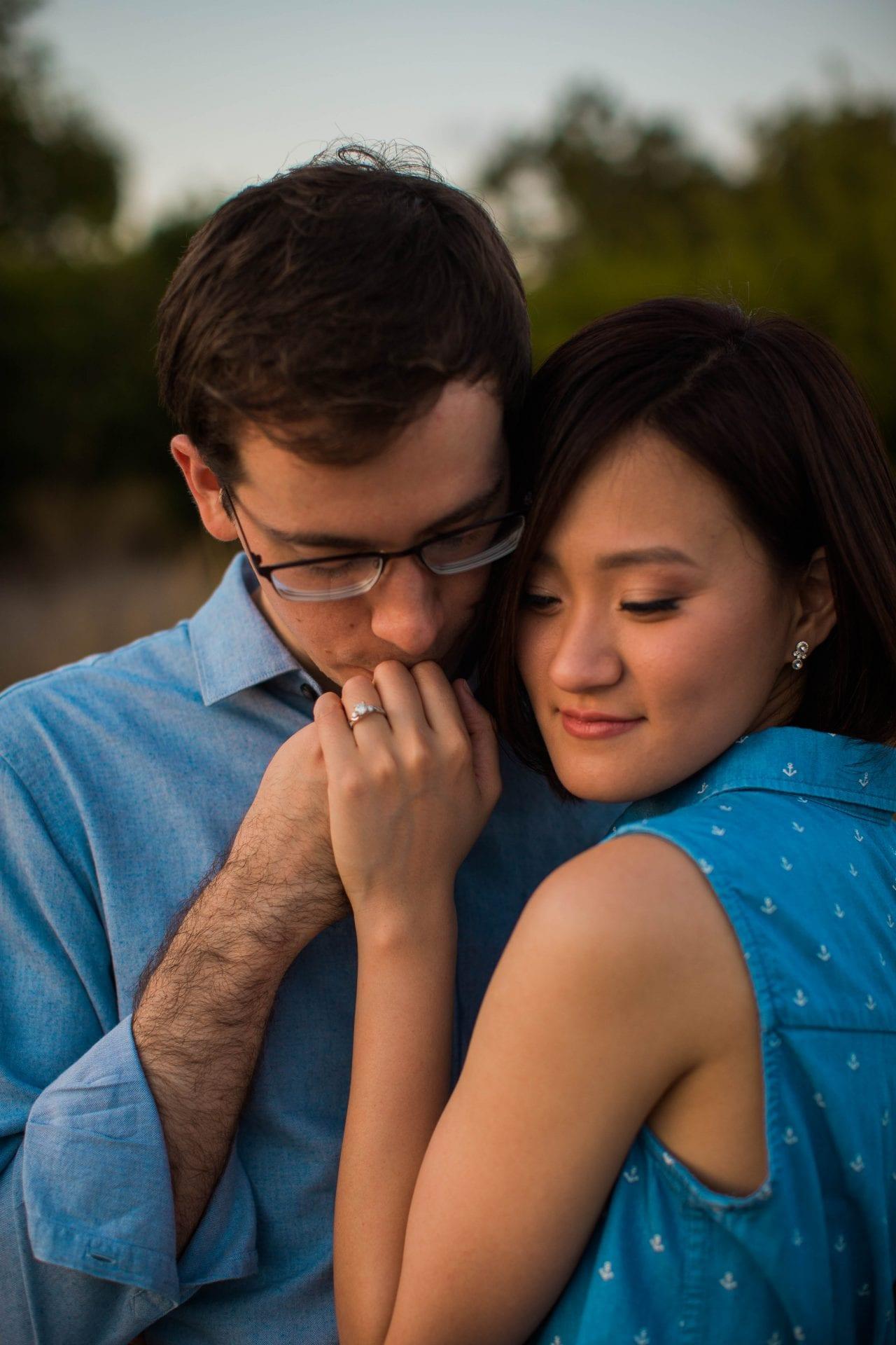 Josh and Tina engagement session at park hand kiss