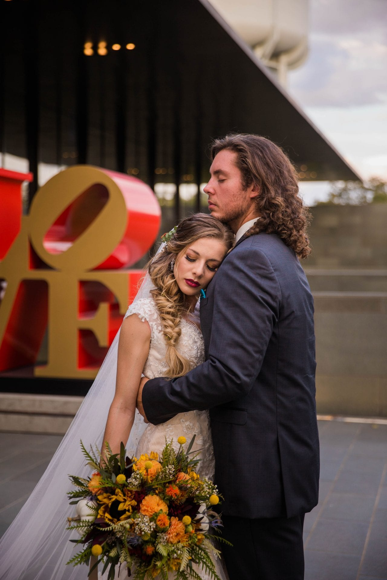 Fall styled shoot at the McNay art museum couple at LOVE letters hug