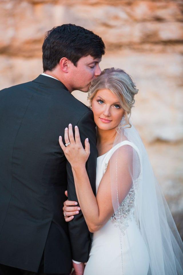 Michele's wedding at La Cantera wedding groom kissing bride rock wall